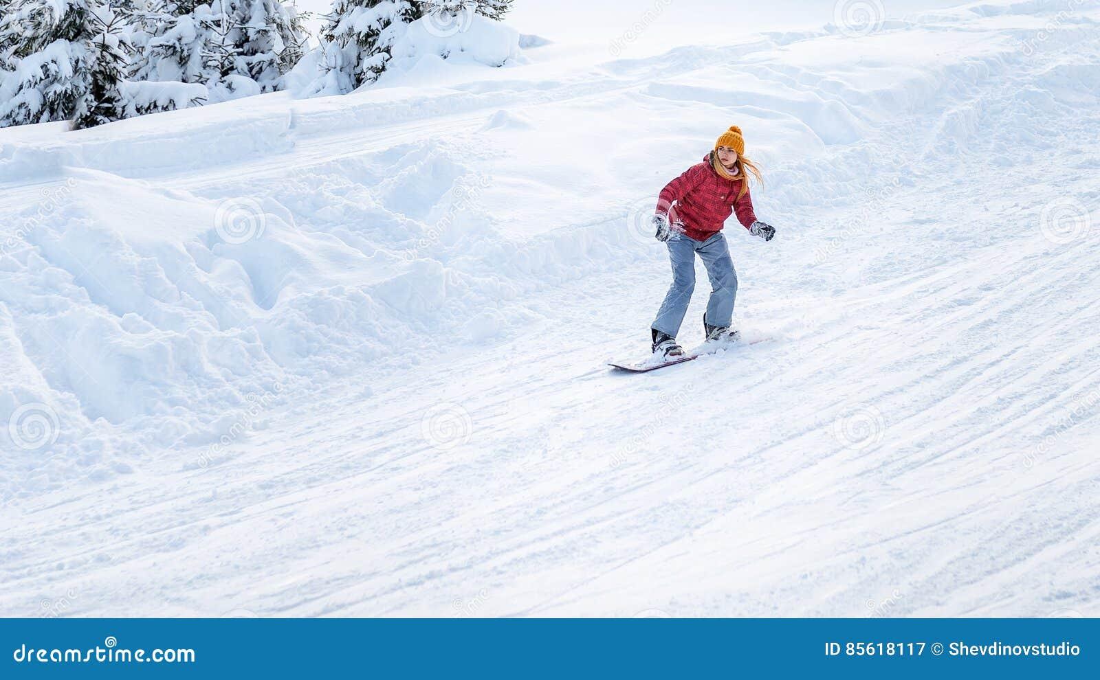 La ragazza va su uno snowboard ai pendii dello sci