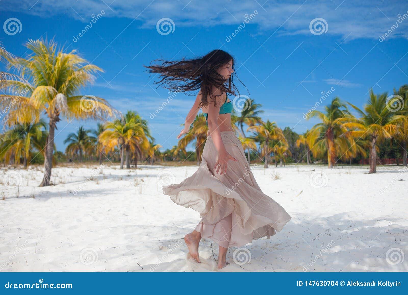 La ragazza viaggia al mare ed è felice Giovane donna castana attraente che balla ondeggiando la sua gonna contro il paesaggio tro