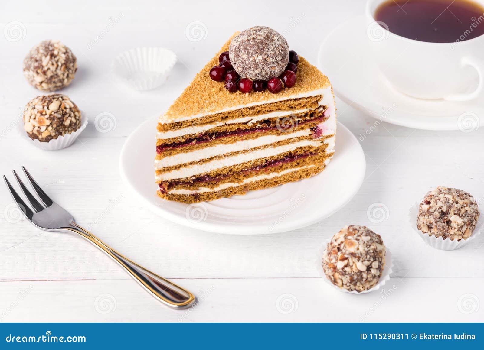 La rebanada de miel hecha en casa sabrosa y los arándanos apelmazan la taza sabrosa del postre del fondo blanco de té