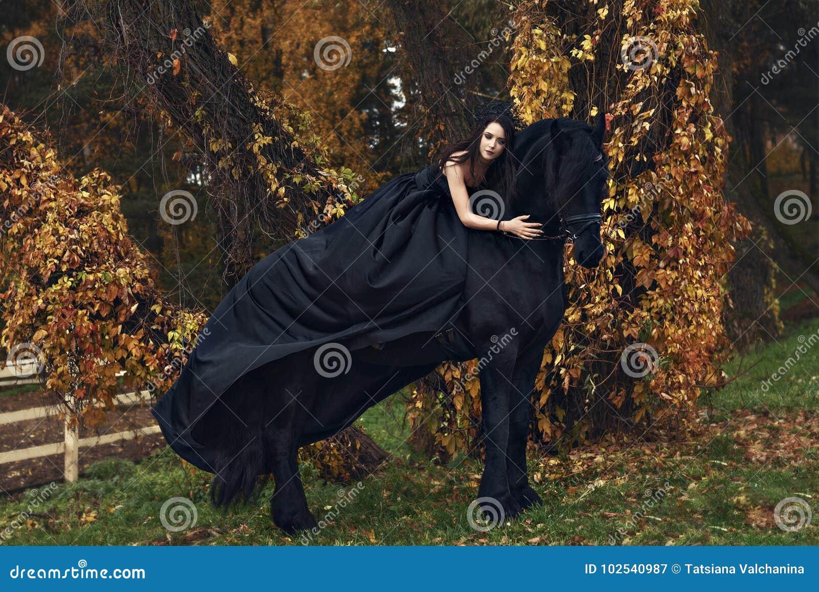 La reine de veuve noire de sorcière étreint son cheval noir dans une forêt d obscurité d horreur