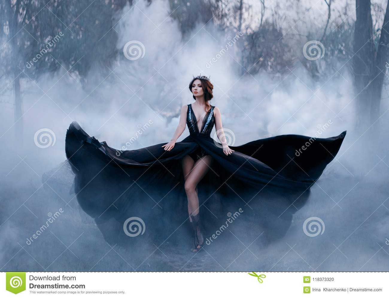 La reine foncée, avec de longues jambes nues, marche brouillard Une robe noire luxueuse évase dans différentes directions, comme