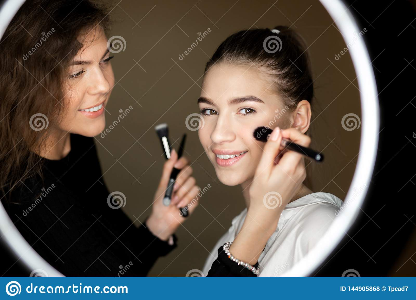 La riflessione nello specchio del truccatore la ragazza affascinante sta facendo il trucco ad una bella ragazza
