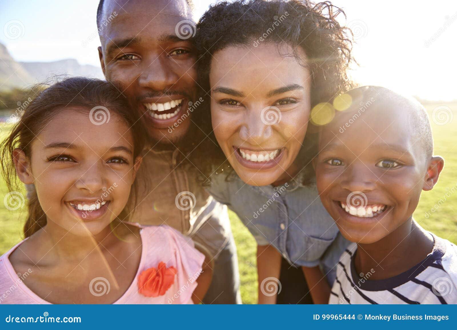 La risa de la familia negra al aire libre, cerca para arriba, detrás encendió el retrato