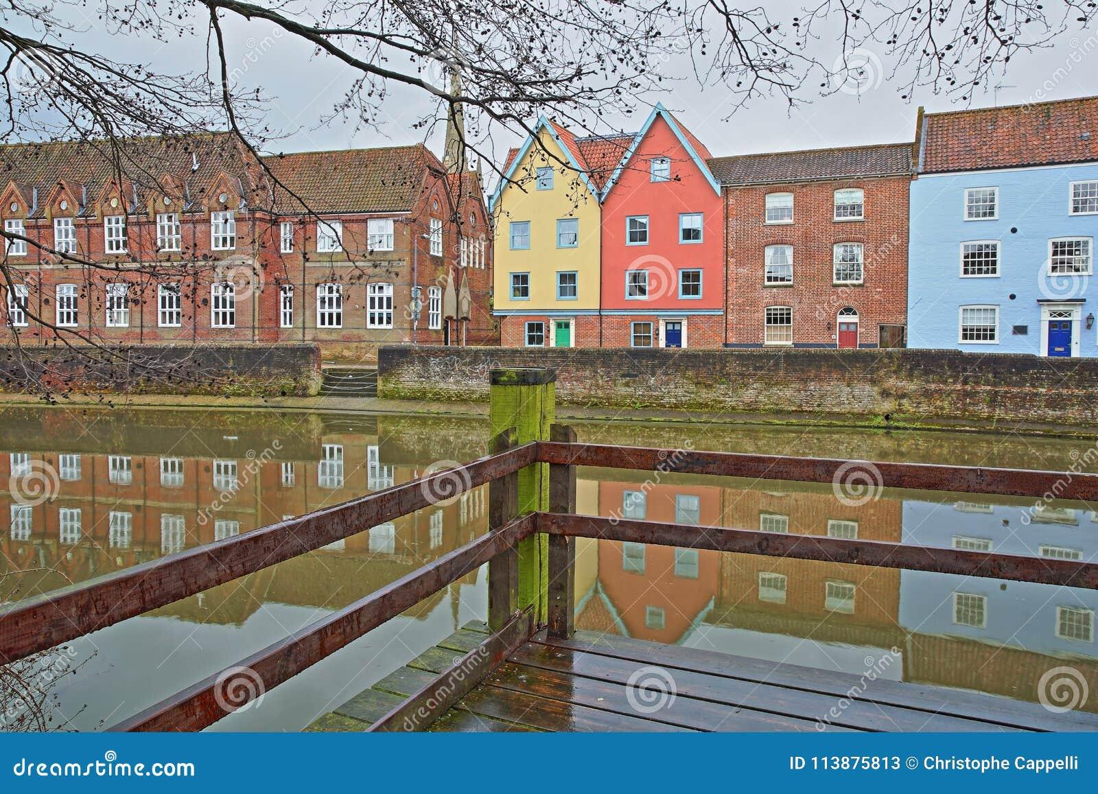 La rivière Wensum de rive avec des réflexions des maisons colorées et la tour et la flèche de la cathédrale
