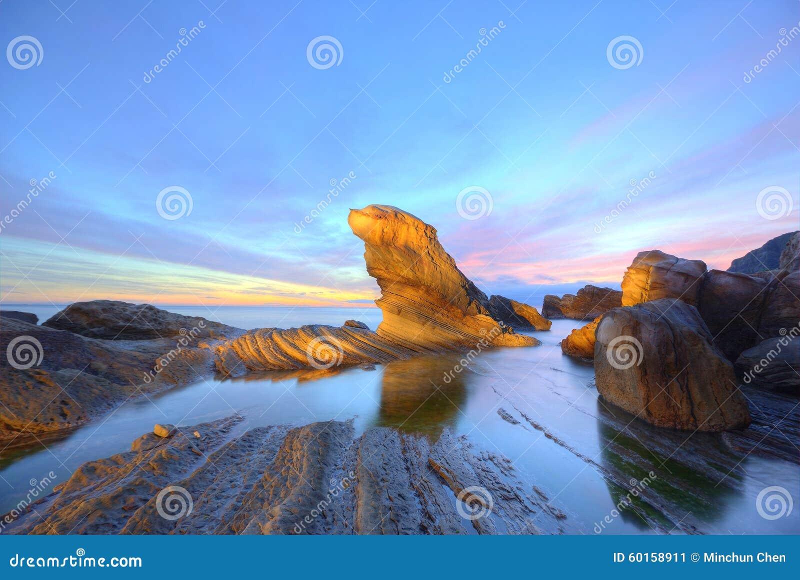 La roccia della guarnizione di pelliccia dalla bella spiaggia illuminata dai primi raggi del sole di mattina alla costa nordica d