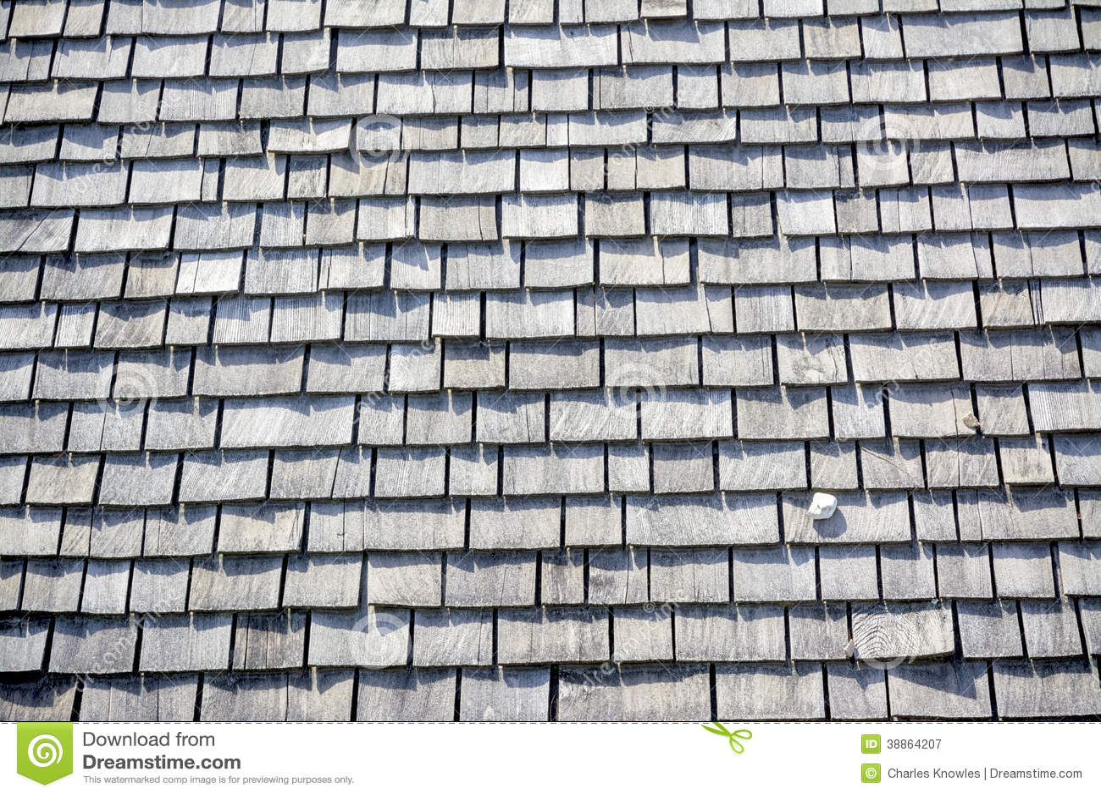 La roccia si siede su un tetto a strati legno