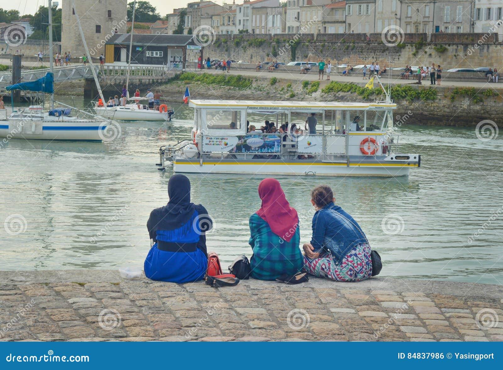 LA ROCHELLE FRANKRIKE - AUGUSTI 12, 2015: Bärande hijab för muslimsk kvinna som ser på de havAtlanten och yachterna