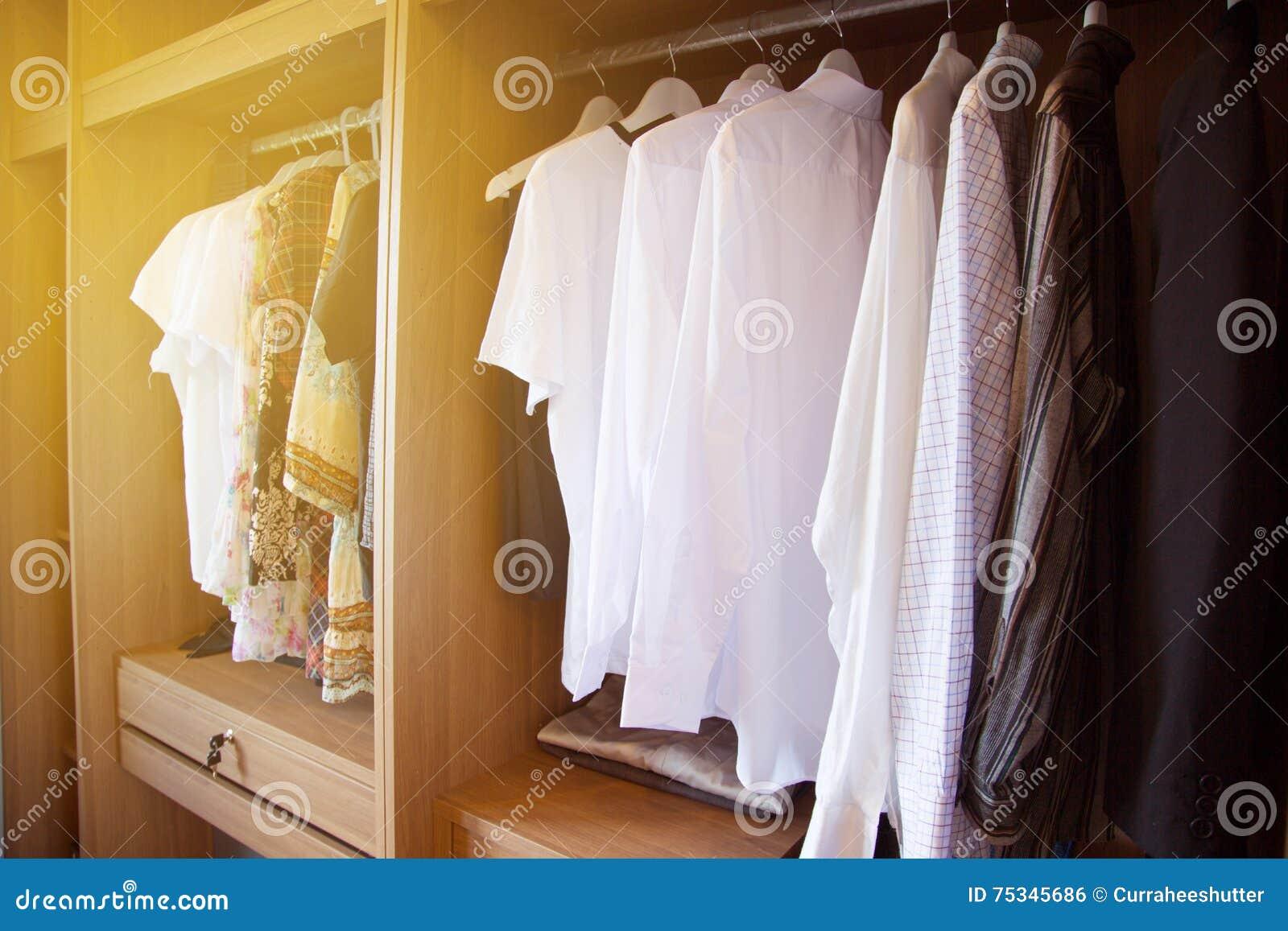 La ropa cuelga en un estante en la ropa de un diseñador tienda, armario moderno con la fila de la ropa que cuelga en guardarropa,