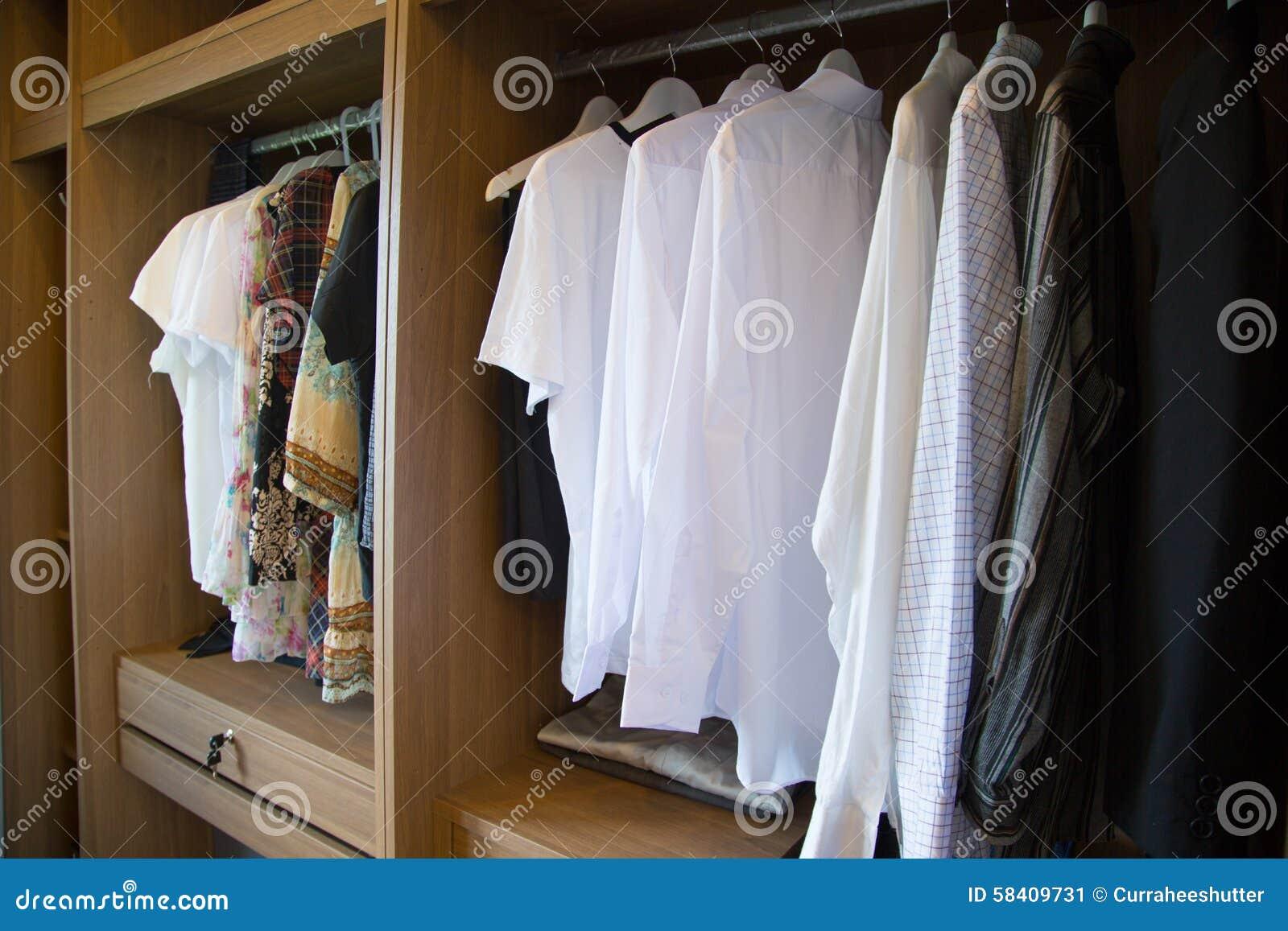 La ropa cuelga en un estante en la ropa de un diseñador tienda, armario moderno con la fila de los paños que cuelgan en guardarro