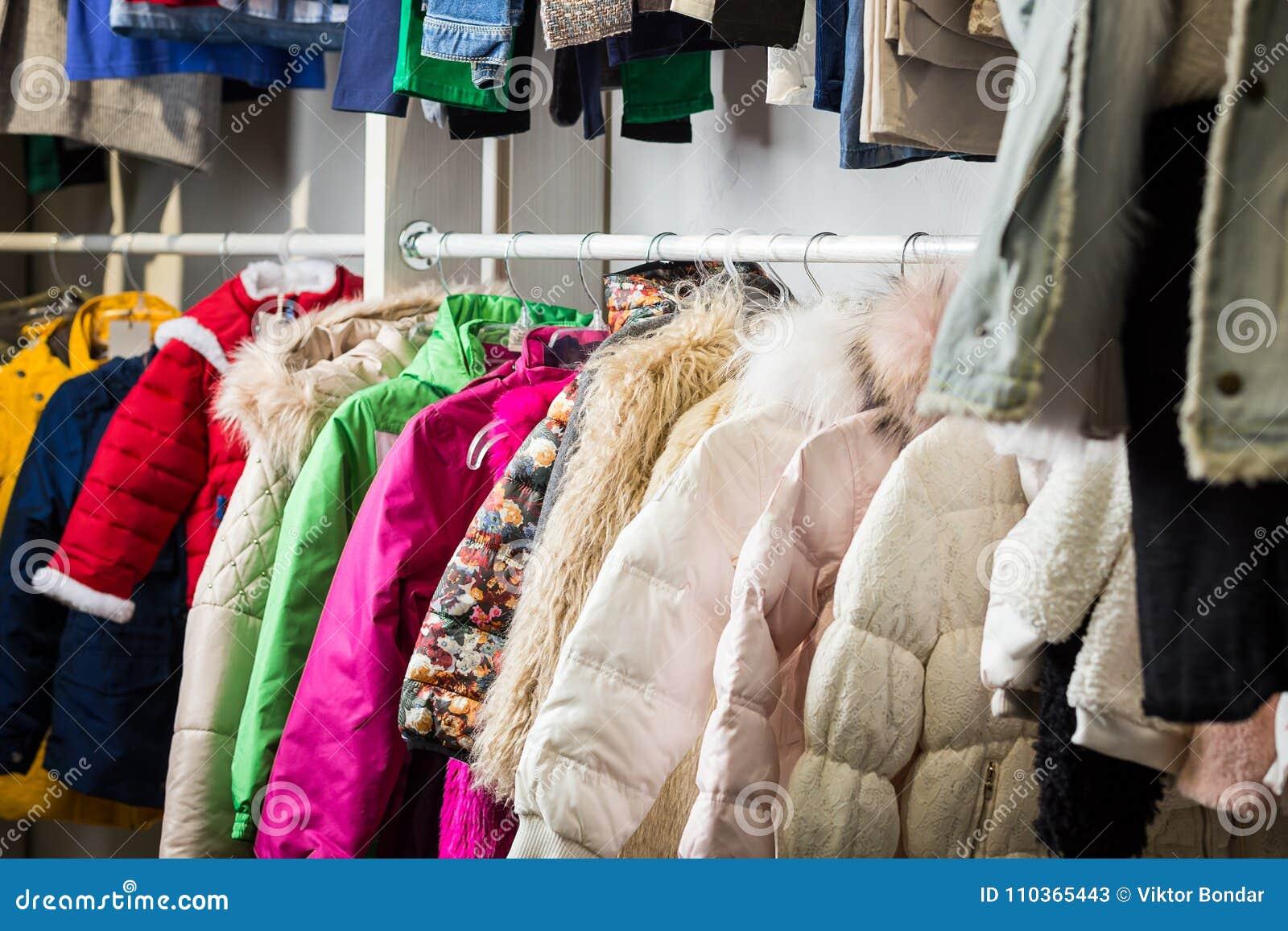 La ropa del bebé cuelga en un estante en una tienda del diseñador