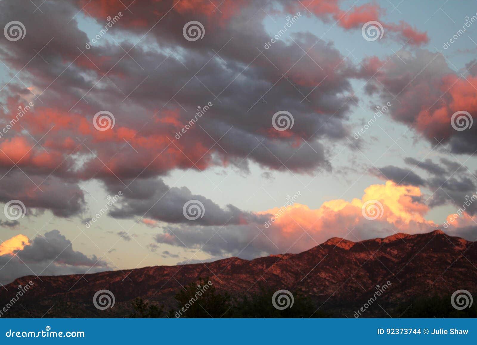 La rosa fuerte imponente se nubla sobre las montañas rojas en la puesta del sol en Tucson Arizona