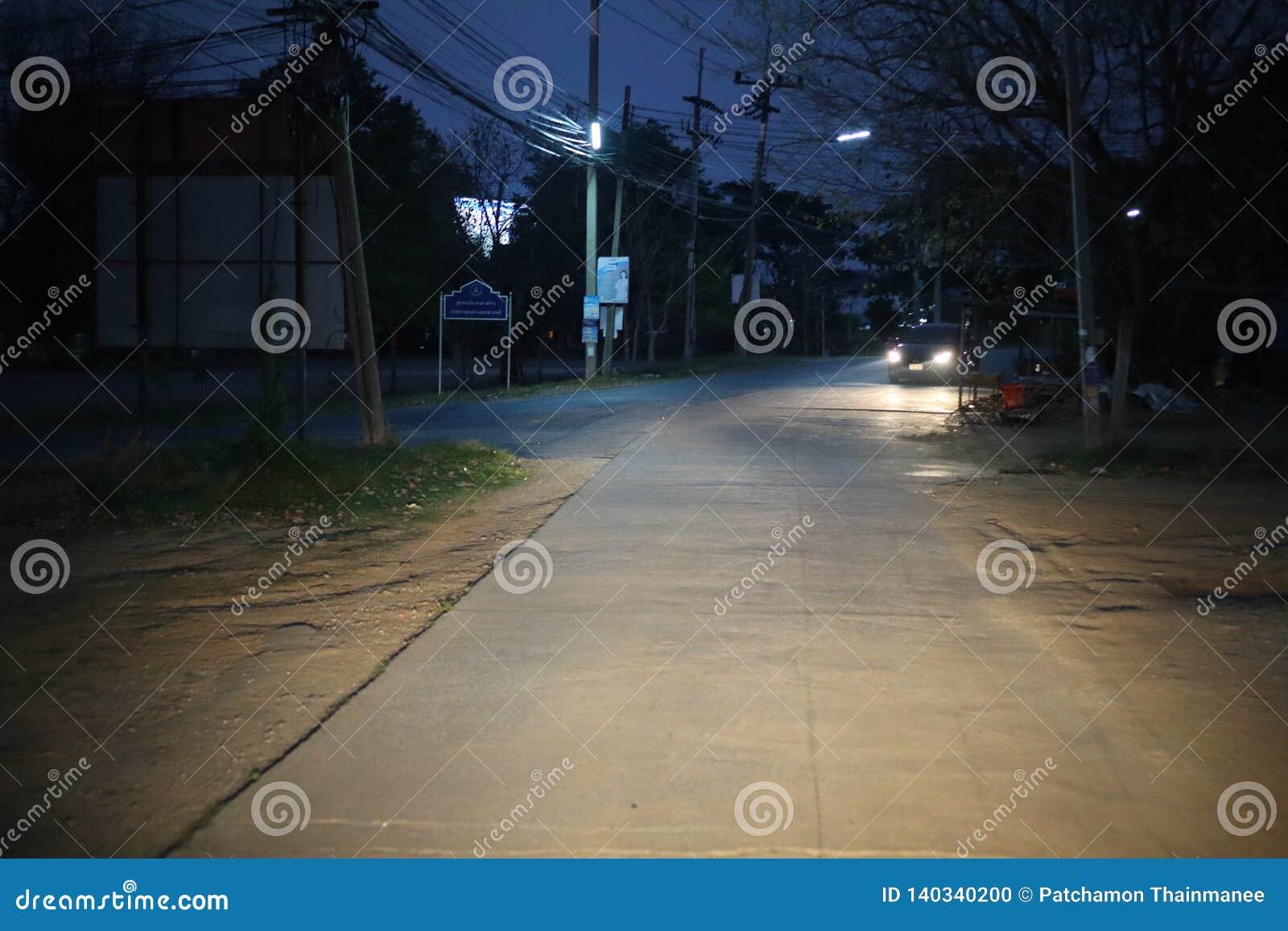 La route principale la nuit, il y a un running back de voiture et il y a une lumière illuminant la manière