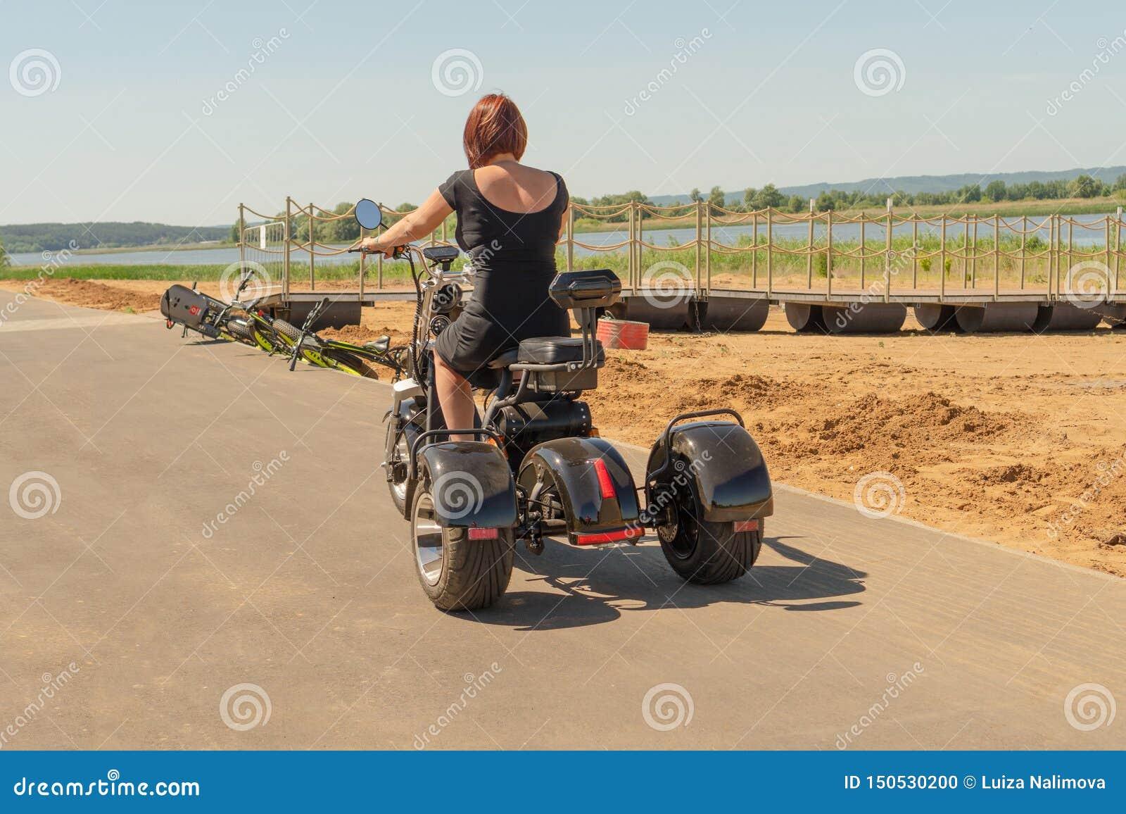 La Russia, Bolgar - 8 giugno 2019 Kol Gali Resort Spa: Una ragazza in un vestito nero con capelli rossi che guidano il suo elettr