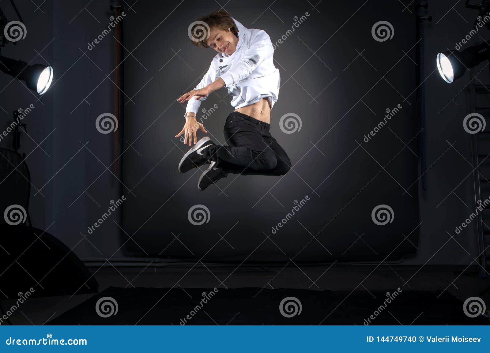 La Russia, Rjazan - 23 06 2018 - Modello dell uomo di Yong che salta nello studio professionale con luce Concetto della scuola de