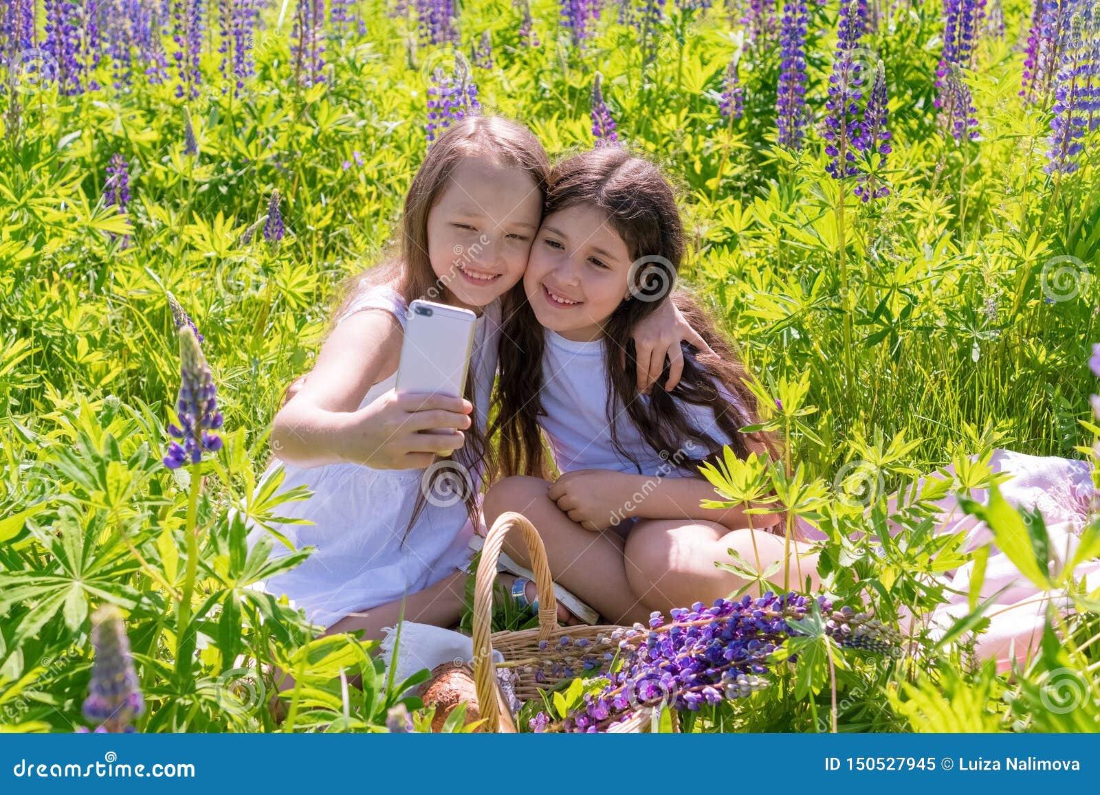 La Russie, Kazan - 7 juin 2019 deux bébés font le selfie à un téléphone parmi des fleurs dans un domaine un jour ensoleillé Le co