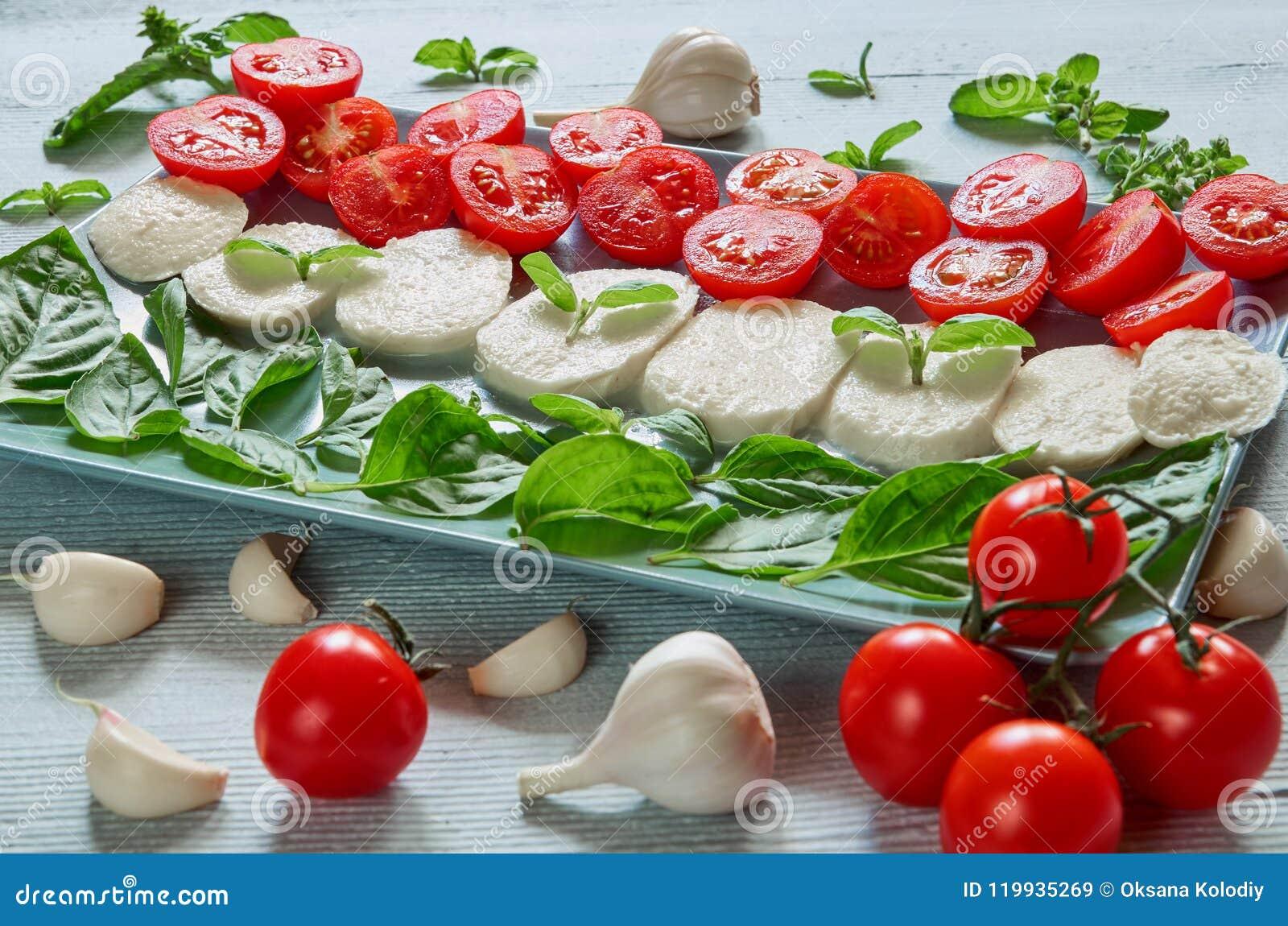 La salade caprese saine avec du fromage coupé en tranches de mozzarella, tomates-cerises, basilic frais part, ail Nourriture ital