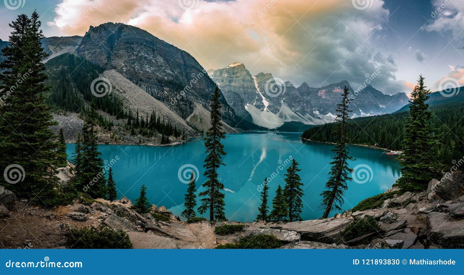 La salida del sol de la opinión del panorama con aguas de la turquesa del lago moraine con pecado encendió las montañas rocosas e