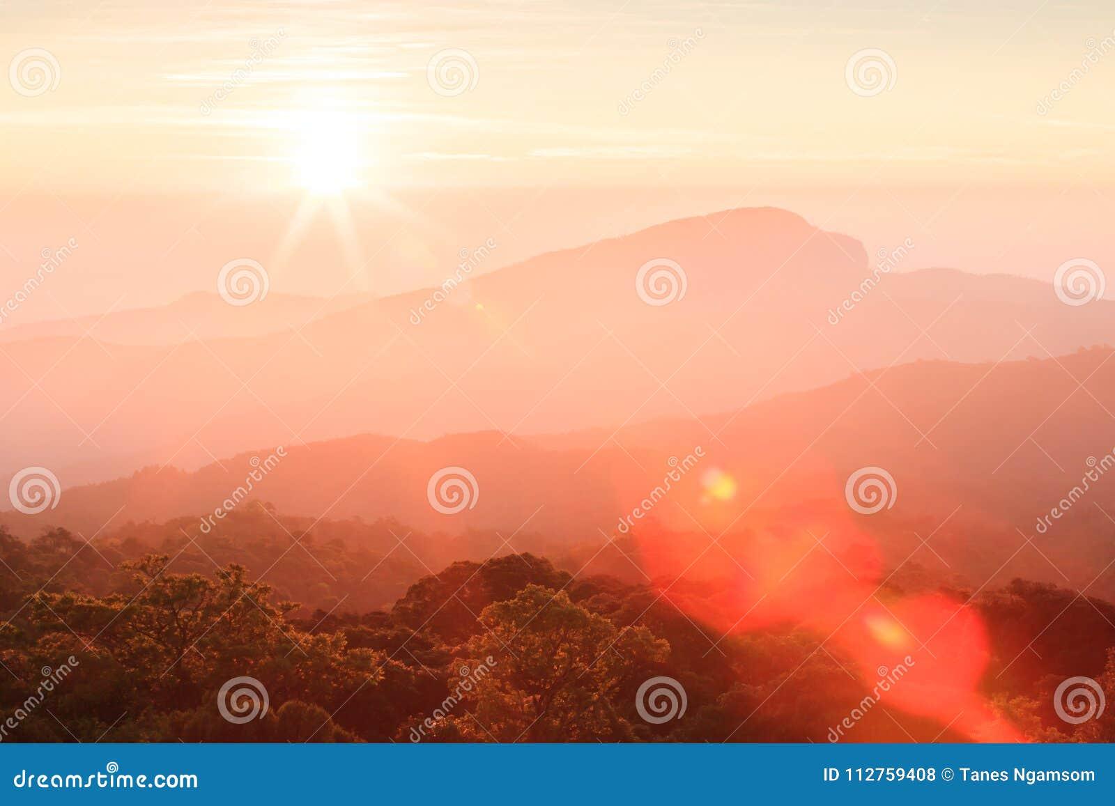 La salida del sol de oro brilla abajo alrededor del toldo de la montaña y del top