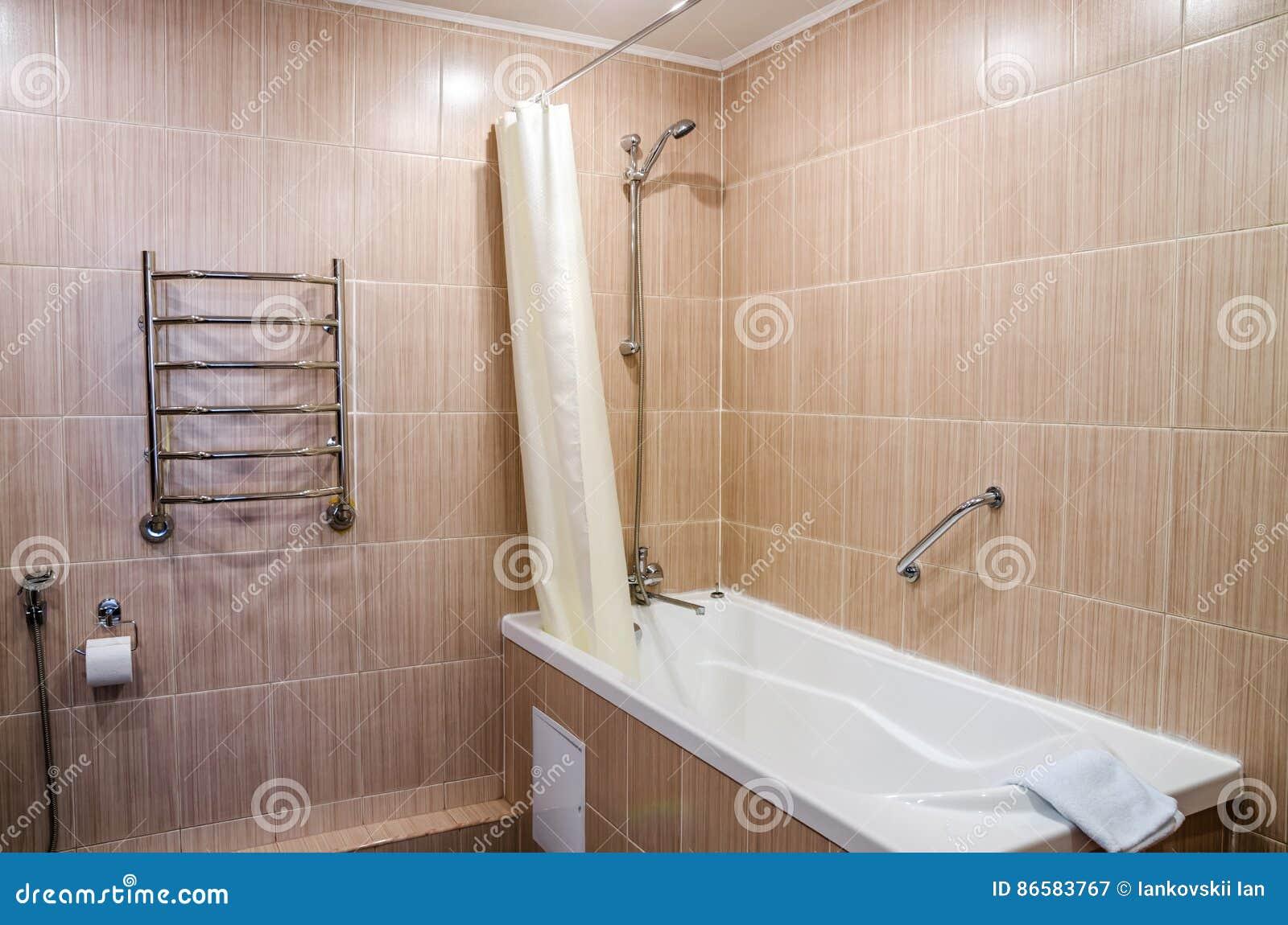 salle de bains dans des couleurs chaudes avec une toilette une baignoire un hairdryer un miroir un dessiccateur pour des vtements un bidet et un