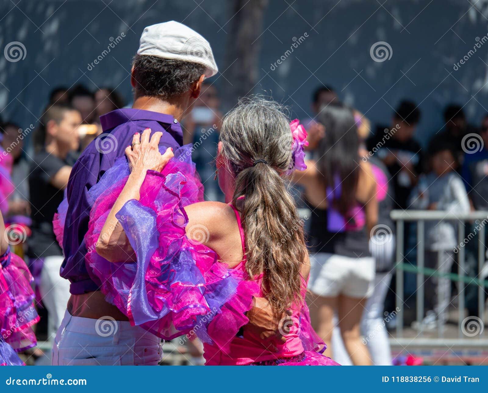 La salsa del hombre y de la mujer baila en el medio de un desfile con una muchedumbre