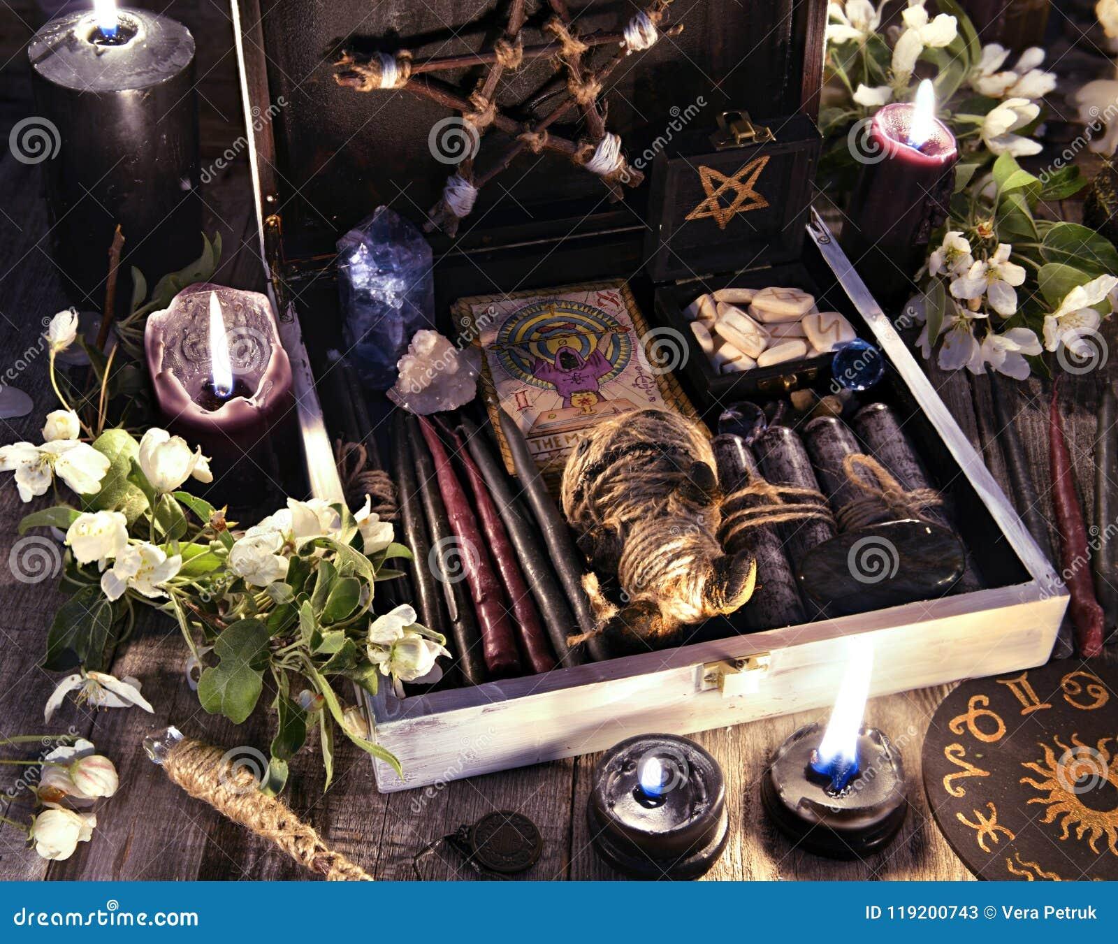 La scatola della strega con le candele, le carte di tarocchi, le rune, la bambola di voodoo e la magia nere obietta con i fiori