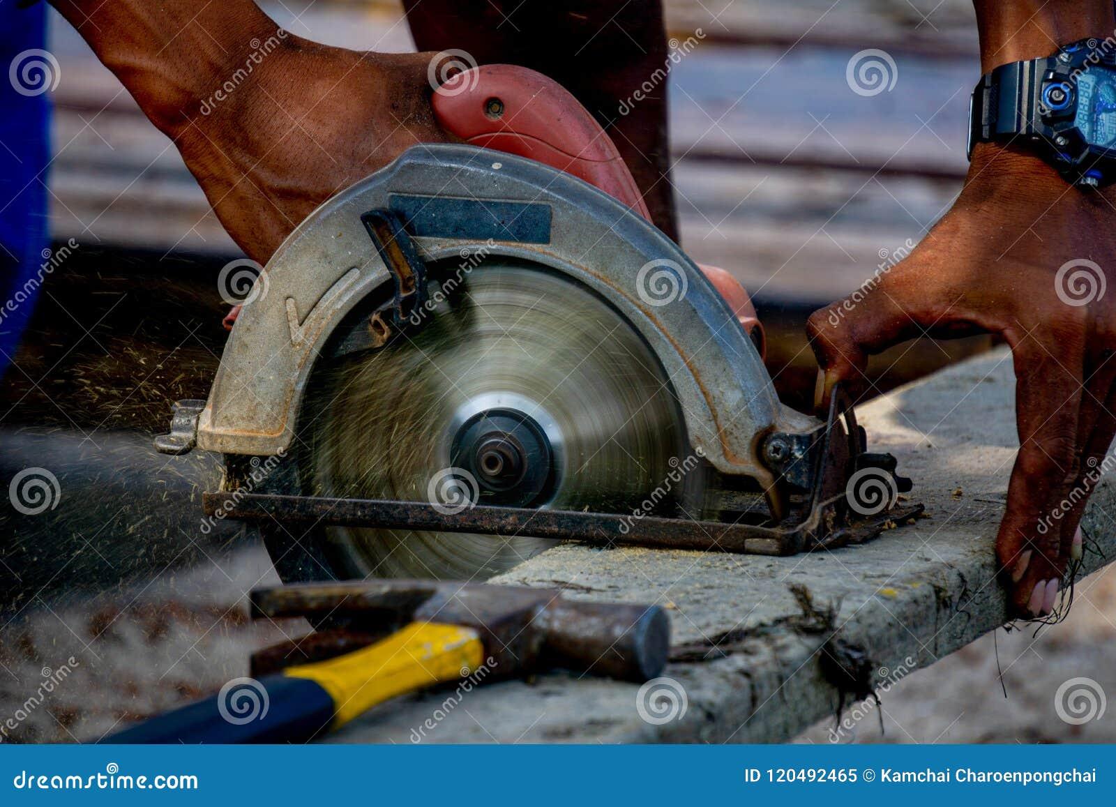 La scie circulaire portative électrique d utilisation d homme coupe un vieux rondin