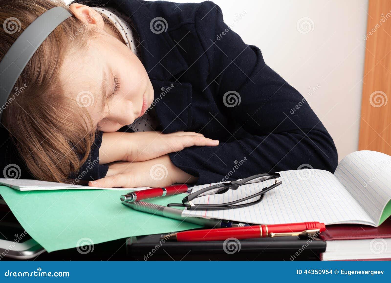 La scolara caucasica bionda dorme sullo scrittorio
