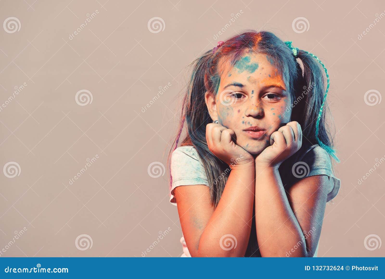 La scolara ha punti della pittura sul fronte Bambini e concetto di creatività