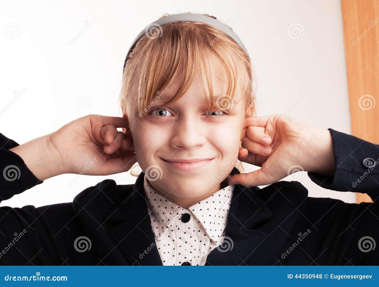 La scolara sorridente bionda tappa le dita in orecchie