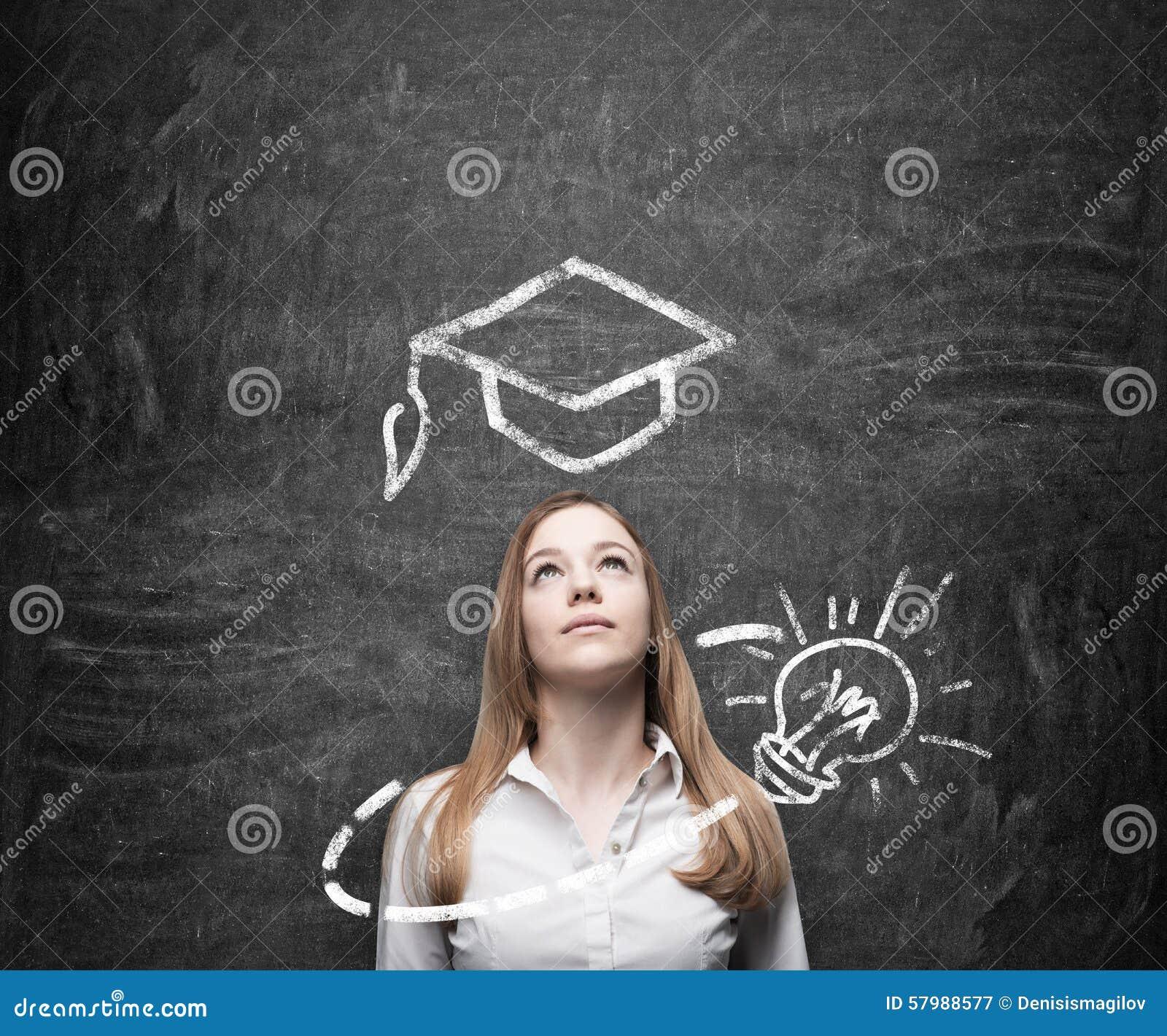 La señora hermosa está pensando en la educación Un sombrero de la graduación y una bombilla se dibujan en la pizarra sobre la señ