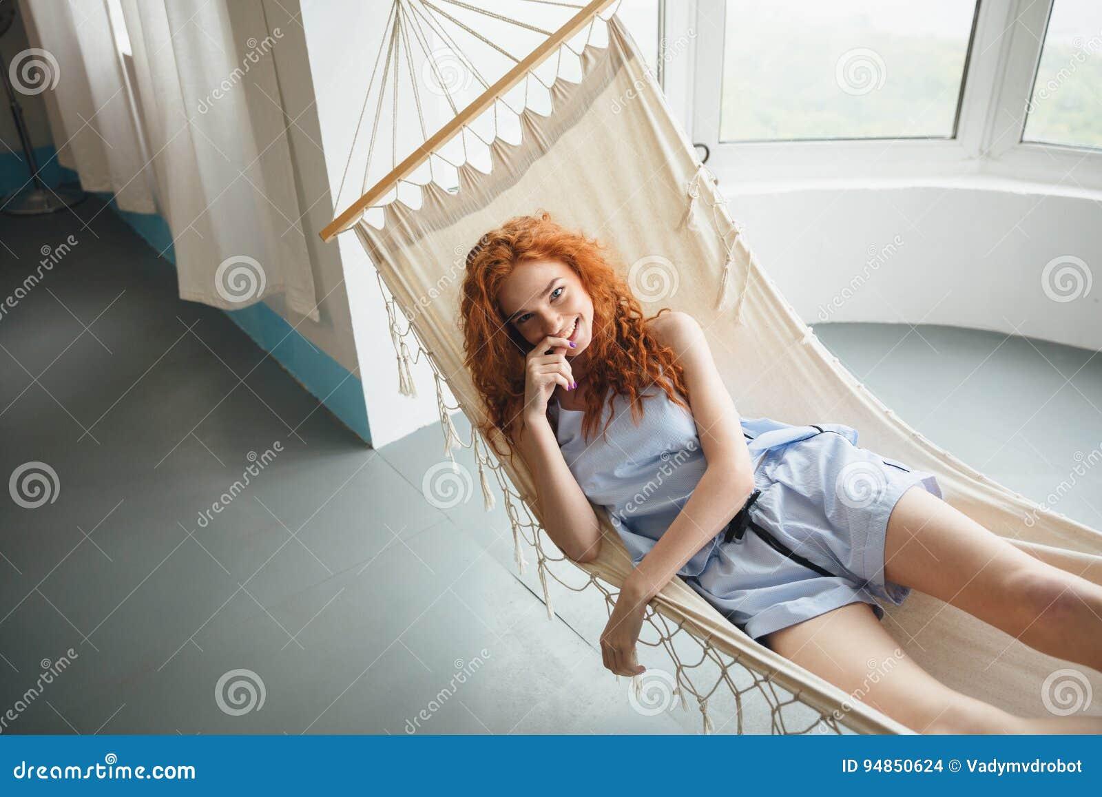 La señora joven alegre linda del pelirrojo miente en la hamaca
