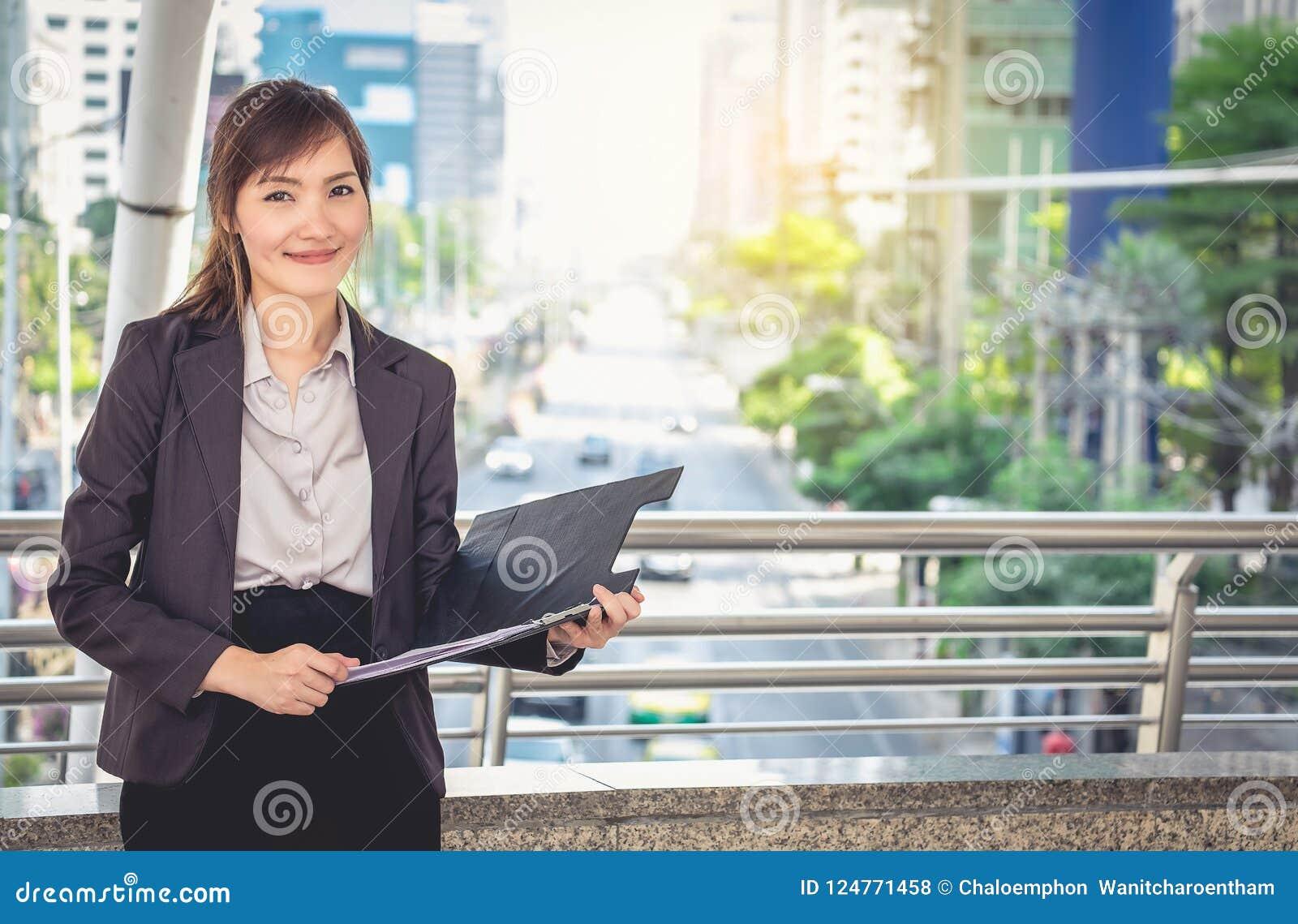 La secretaria se está colocando sonriente y que sostiene un fichero con un grande