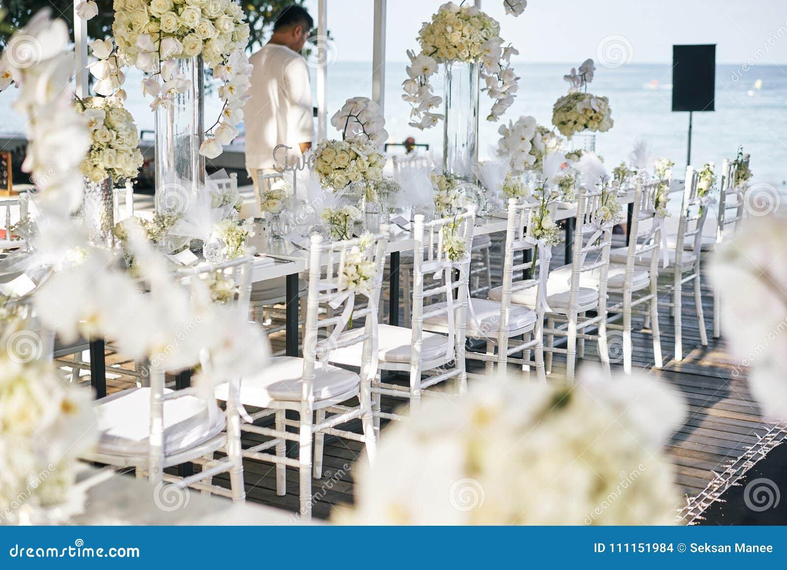 La sede di nozze per la tavola di cena di ricezione decorata con le orchidee bianche, rose bianche, fiori, sedie floreali e bianc