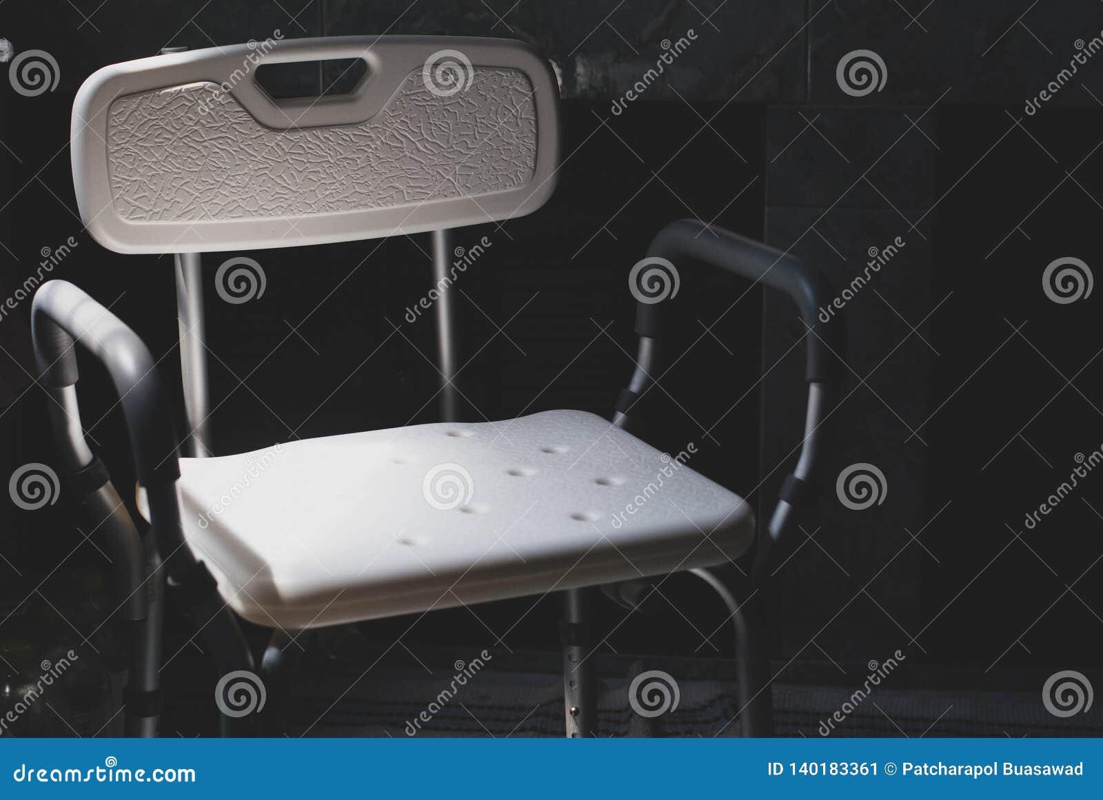 La sedia di bagno di plastica per l inondazione dei disabili o dell anziano messa nella luce lasciante scura viene dalla parte di