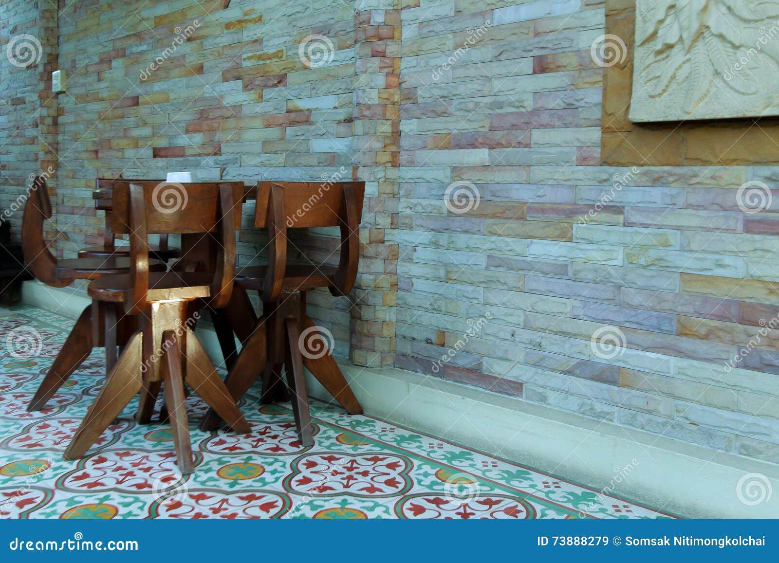 La sedia e la tavola di legno sulle piastrelle per pavimento si