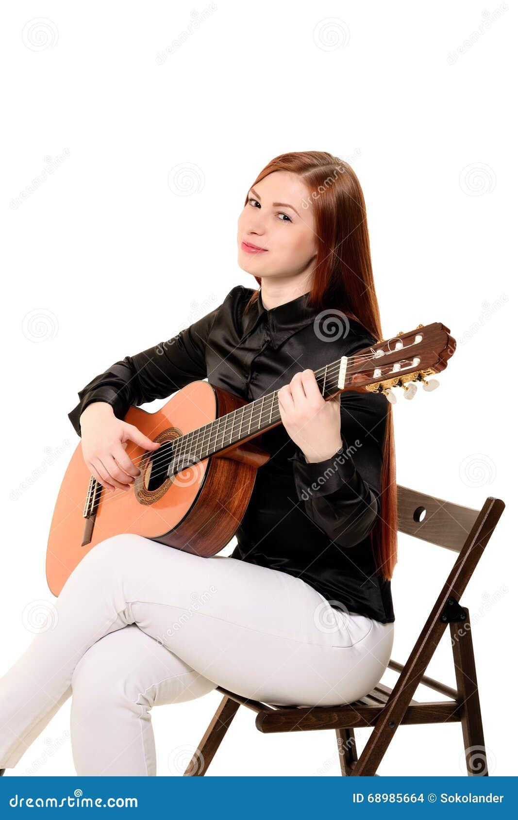 La sentada de la mujer joven presenta en el estudio que lleva a cabo un guit clásico