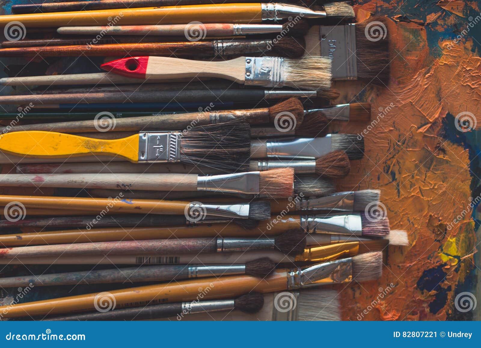 La serie de diversas brochas de madera del tamaño que mentían en la paleta con la pintura de aceite vieja agrietó la textura en e