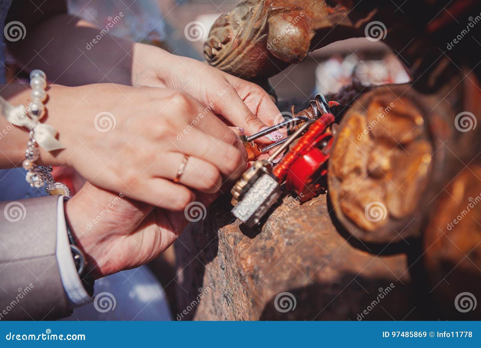 La serratura in mani delle persone appena sposate