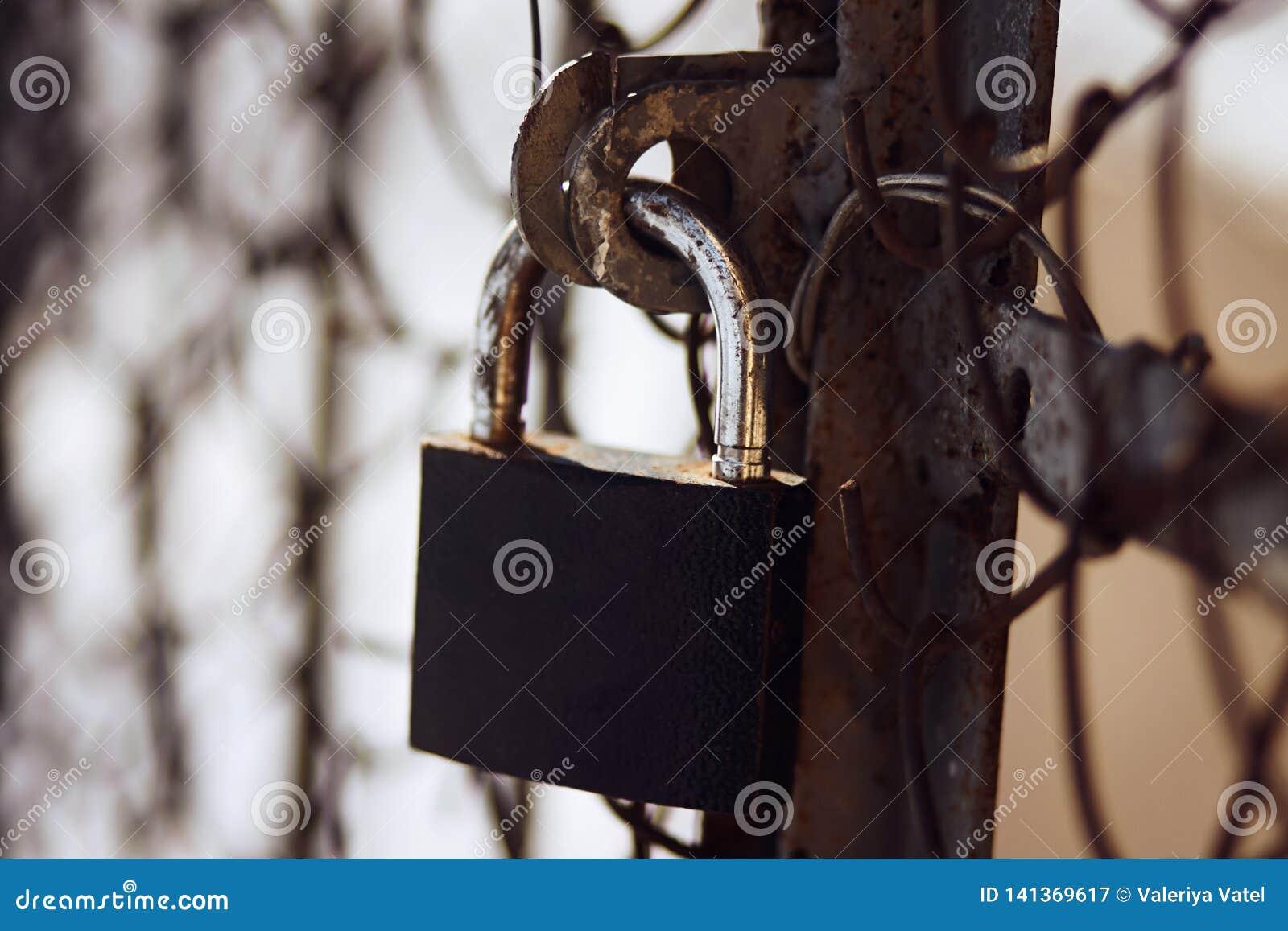 La serrure minable rouillée ferme la vieille porte rouillée