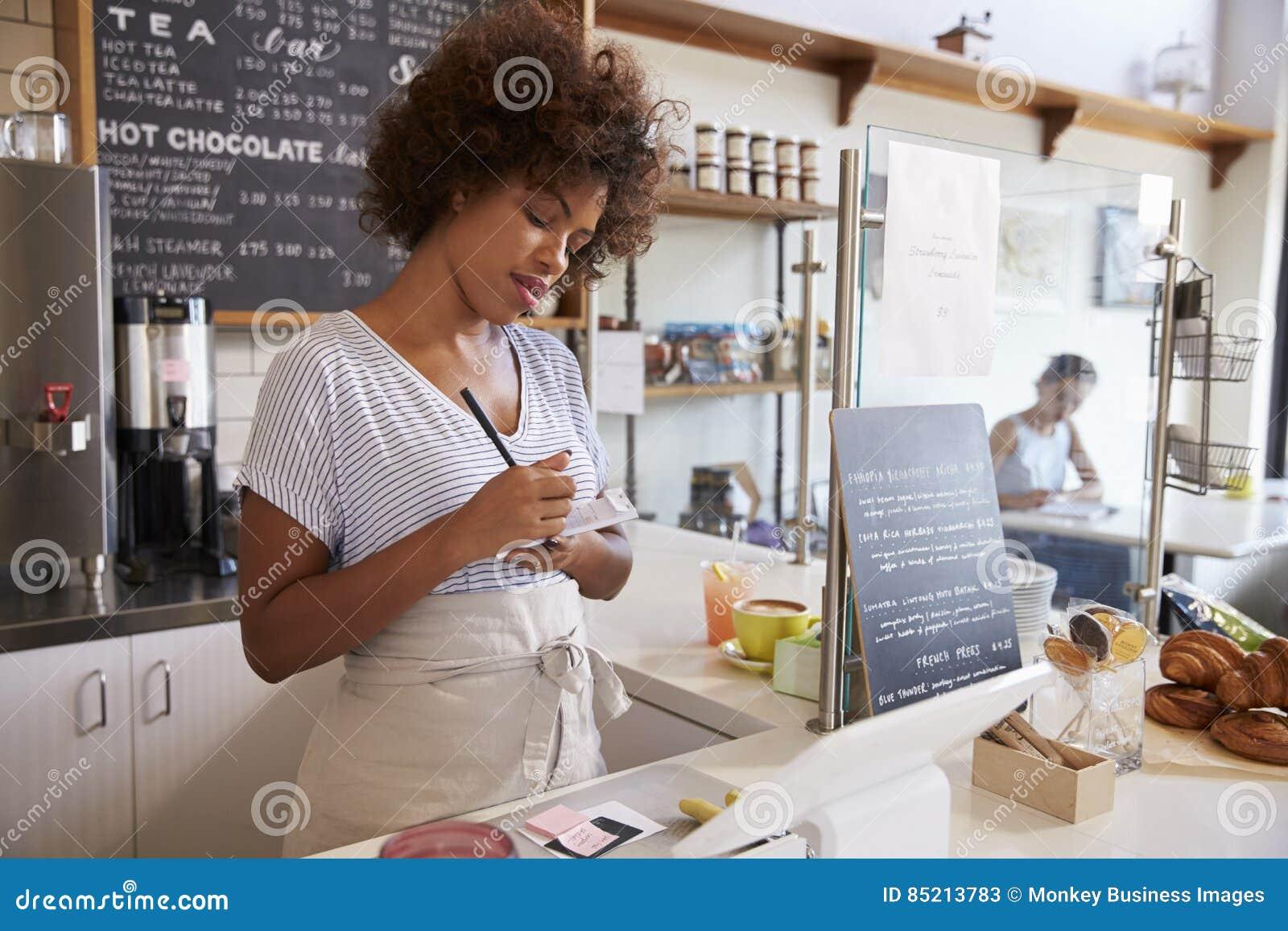 La serveuse notant un ordre à un café, se ferment