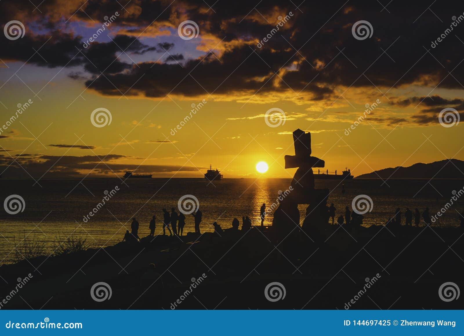 La silhouette d Inukshuk avec le coucher du soleil opacifie des milieux de ciel