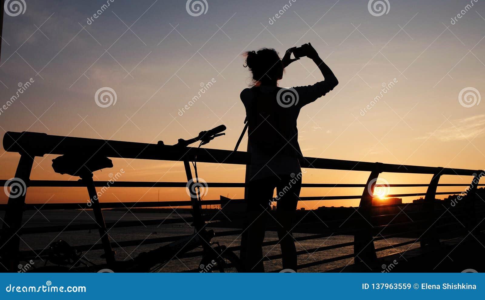 La Silhouette Dune Fille Prend Des Photos Du Coucher Du