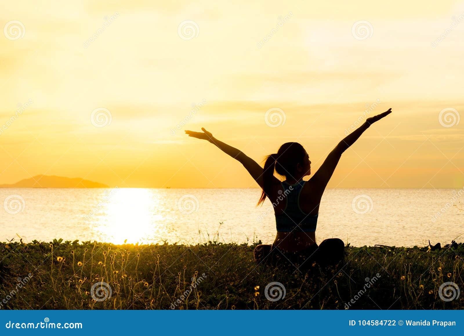 La silhouette de femme de mode de vie de yoga de méditation sur le coucher du soleil de mer, détendent essentiel