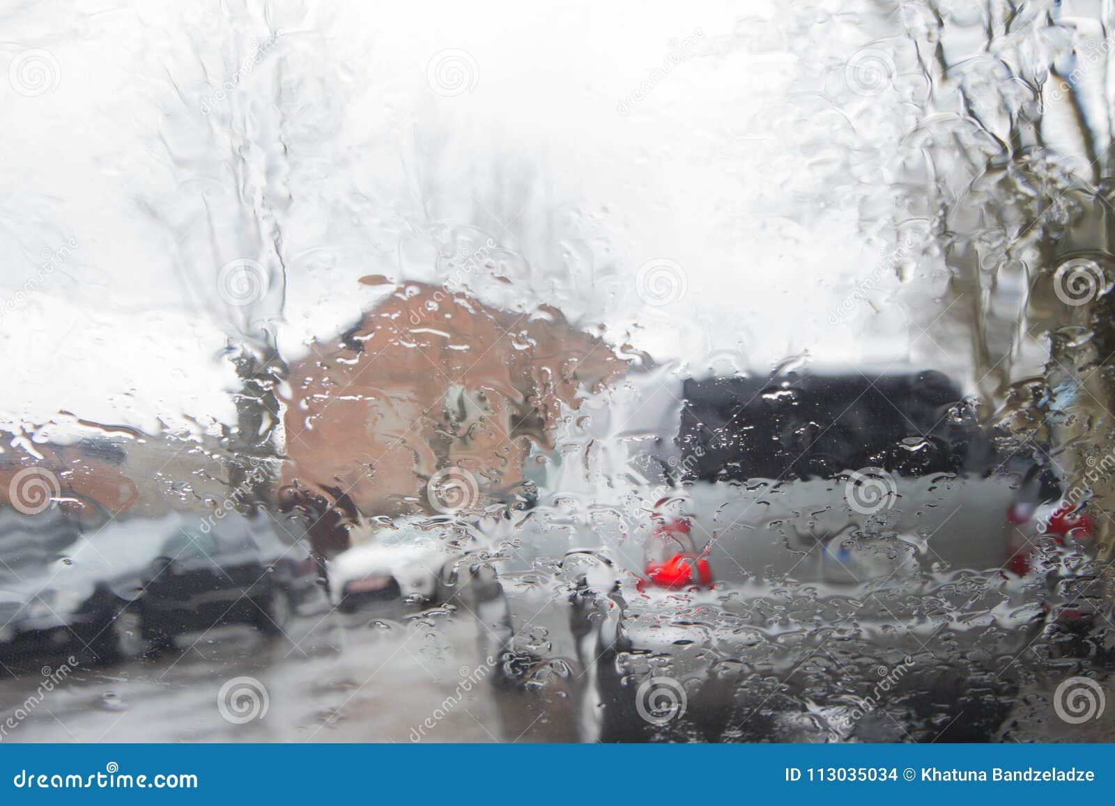 La silueta borrosa del coche vista a través del agua cae en el parabrisas del coche Días lluviosos