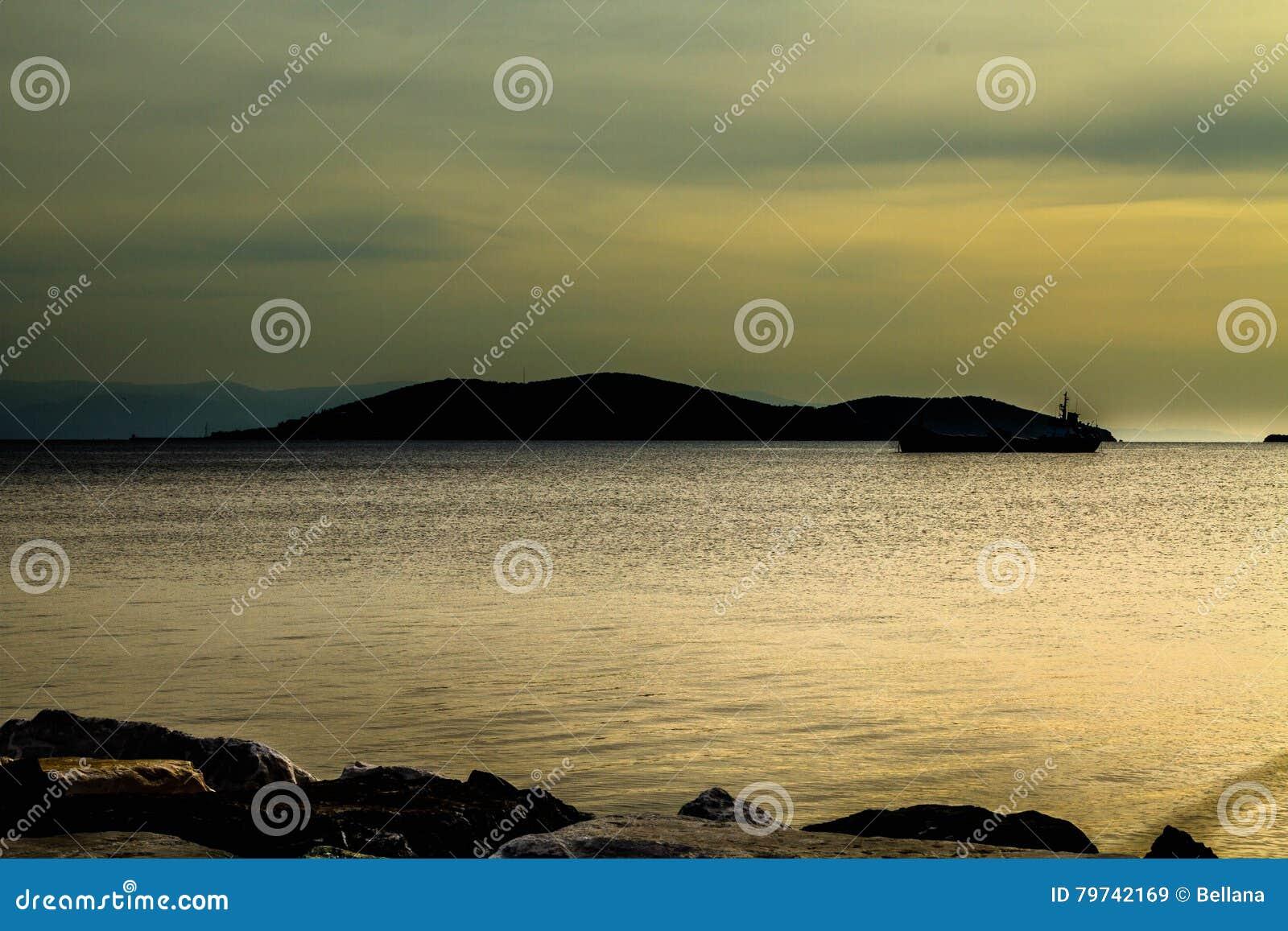 La silueta de la isla en el mar en la puesta del sol