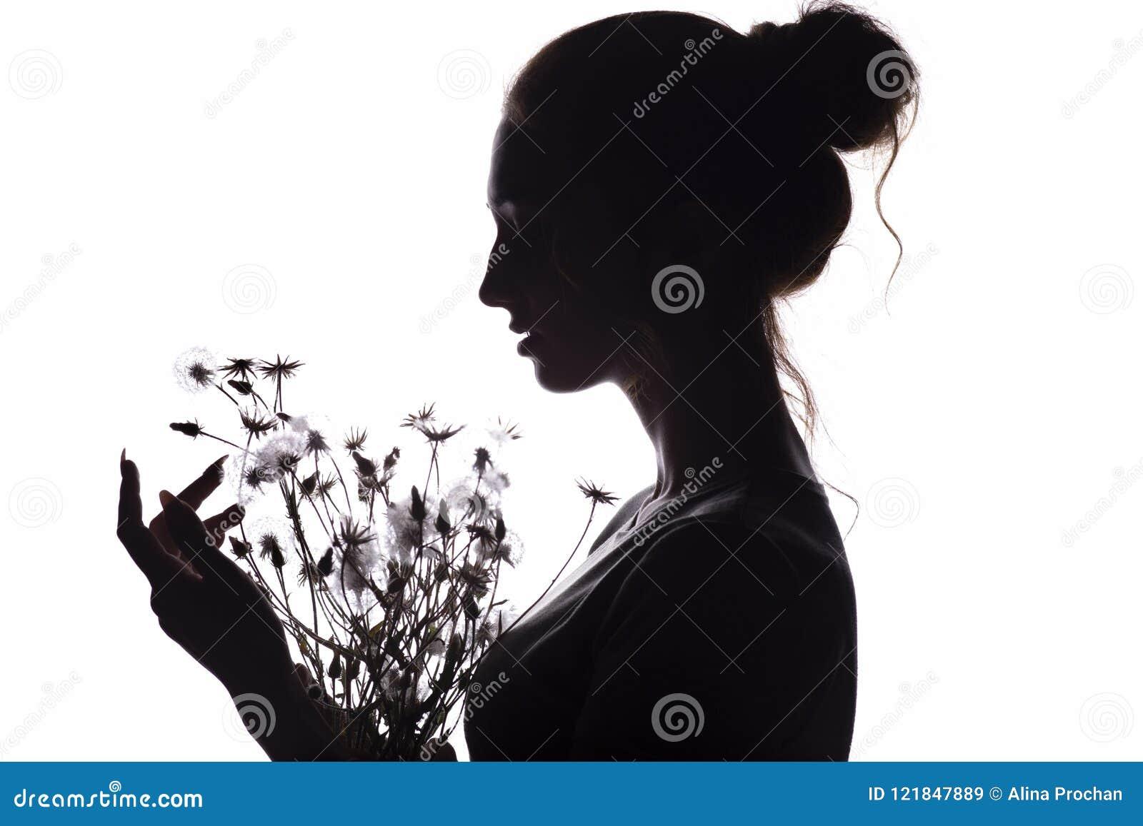 La silueta de la muchacha con un ramo con de dientes de león, cara de la mujer joven en un blanco aisló el fondo