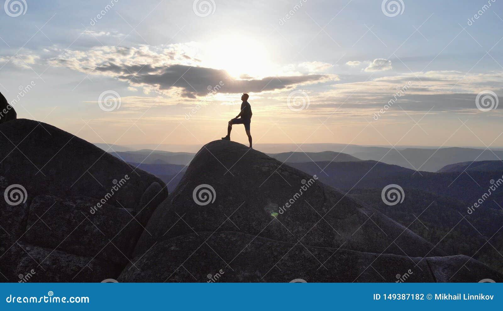 La silueta de un hombre que se coloca triunfante en un top de la montaña en la puesta del sol