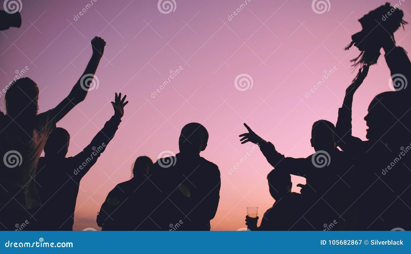 La siluetta dei giovani di dancing del gruppo ha un partito alla spiaggia sul tramonto