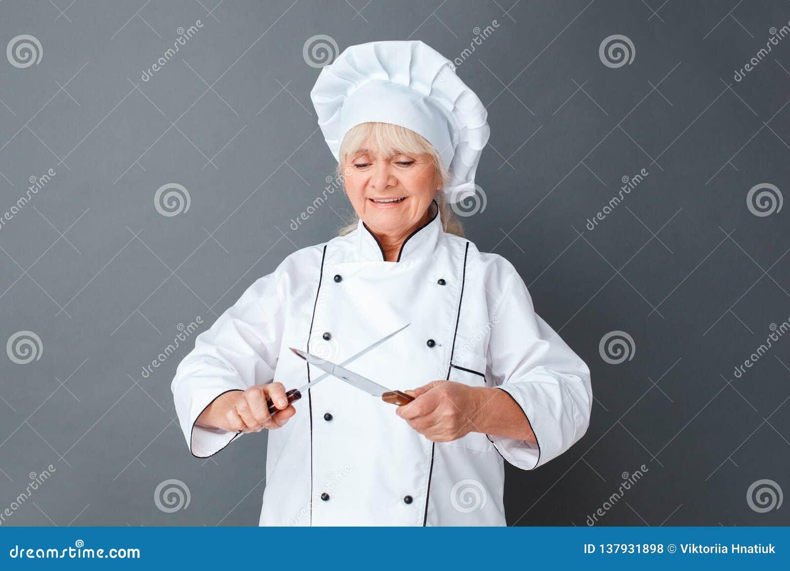 La situación mayor del estudio del cocinero de la mujer en los cuchillos afiladores grises concentró alegre