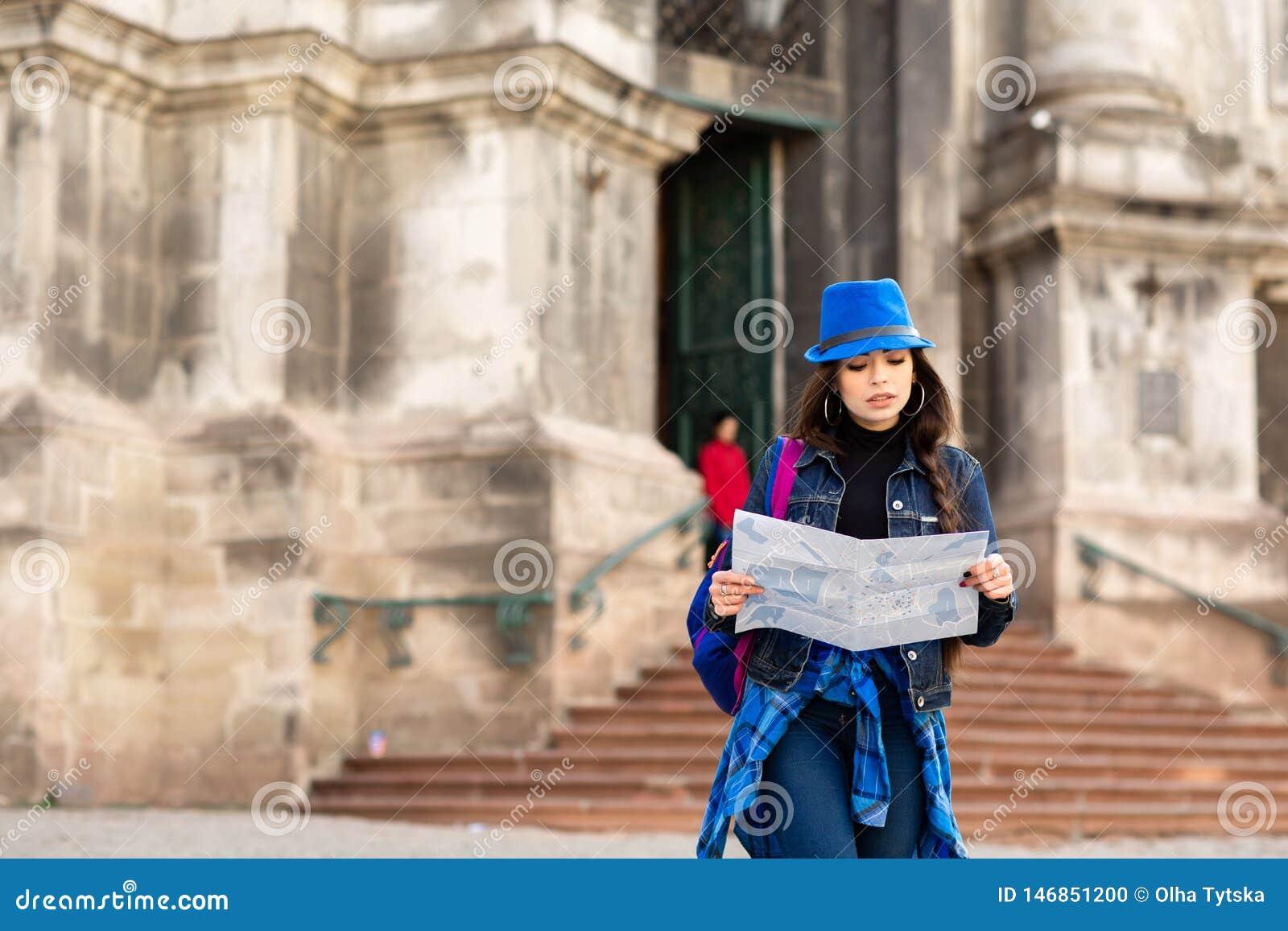 La situaci?n de la mujer joven cerca de la iglesia en la ciudad vieja Lviv, y sostiene un mapa a disposici?n ucrania
